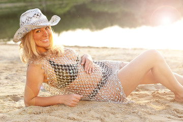 Attraktive junge Frau mit Cowboyhut am Strand- girl on the beach