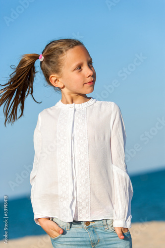 Cute girl with ponytails at seaside.