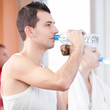 Man and woman drinking water after sports in gym