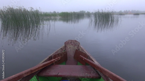 wooden boat with oars on lake and morning mist