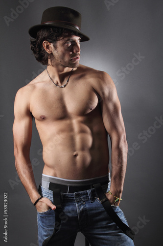 Shirtless model with hat and suspenders