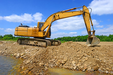 Excavator on the work to strengthen the shoreline of the river.