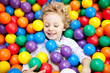 A young blond girl child having fun playing with сolorful  balls
