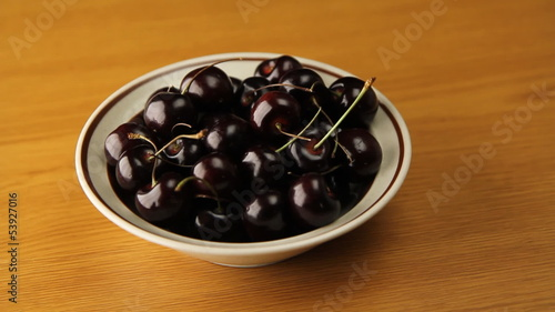 Bowl of cherries rotating on wood grain background.