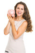 Happy young woman showing piggy bank