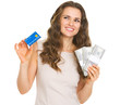 Thoughtful young woman with credit card and dollars
