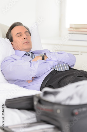 Tired of traveling. Tired mature businessman sleeping on the sof