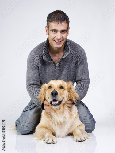 a handseome guy and his dog playing. Good friends