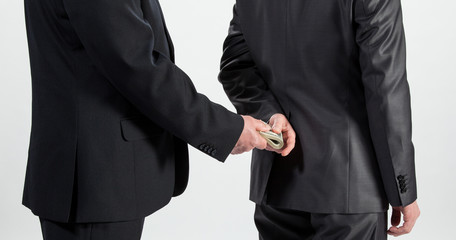 Businessman giving a bribe, neutral background