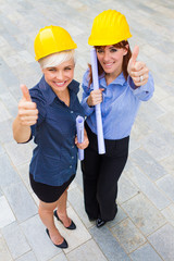Female constructors making positive thumb gesture while smiling