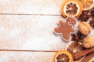 Gingerbread cookie and spices on sugar background.