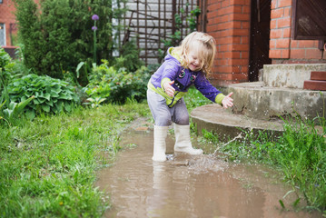 Funny 2 years old baby girl playing in puddle.