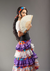 Portrait of beautiful Gypsy girl with fan, gray background
