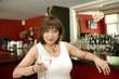 Frau in weißem Kleid sitzt an der Theke einer Bar
