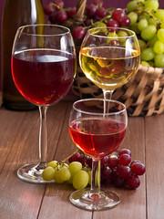 Wein im Weinglas mit einem Korb Weintrauben im Hintergrund
