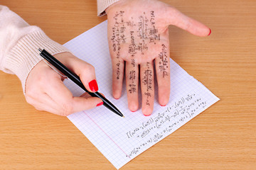 Write cheat sheet on hand on wooden table close-up