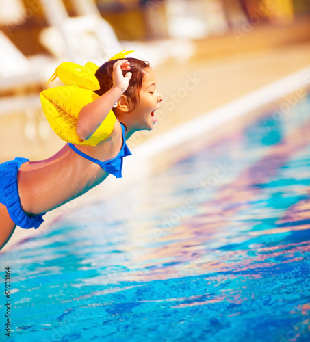 Little girl jumping into the pool