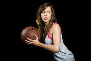 Young blonde in a defense position with a basketball