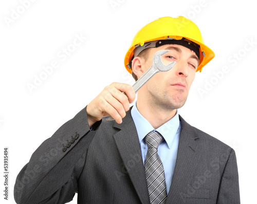 Young businessman in helmet with wrench isolated on white.