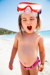 Bambina al mare con maschera che sbadiglia
