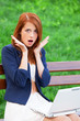 Redhead girl sitting at the bench with notebook