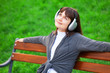 Brunette girl with headphones sitting at the bench in the park.
