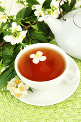 Cup of tea with jasmine, on wicker mat background
