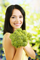 Girl with fresh broccoli on natural background