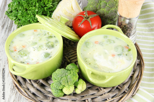 Cabbage soup in plates on braided tray on napkin on wooden