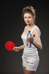 Young woman holding a bottle of water and tennis racquet