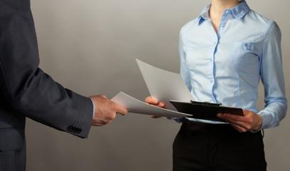 Businessman and businesswoman interchange of documents
