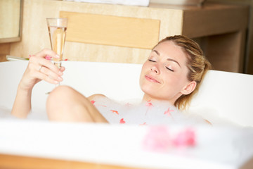 Woman Relaxing In Bath Drinking Champagne