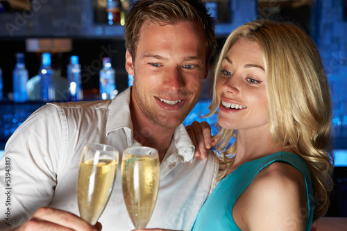 Couple Enjoying Glass Of Champagne In Bar