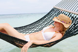 Woman Wearing Bikini And Sun Hat Relaxing In Beach Hammock