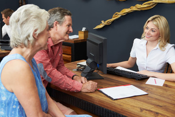 Hotel Receptionist Helping Senior Couple To Check In