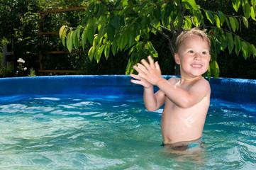 Kleiner Junge spielt im Pool