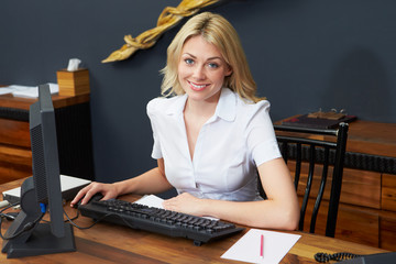 Hotel Receptionist Working At Computer