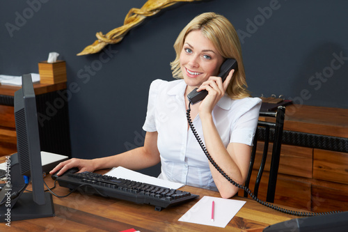 Hotel Receptionist Using Computer And Phone