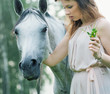 Young woman stroking spotted horse
