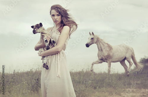 Young brunette lady holding little lamb