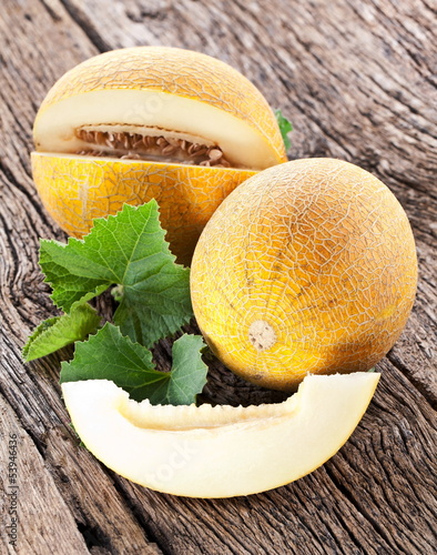 Melon with slices and leaves on a old wooden table.