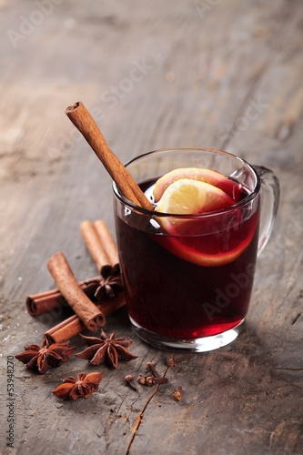 Mulled wine and spices on wooden background. Selective focus.