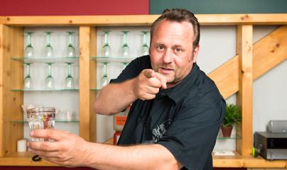 kellner zeigt entschlossen mit dem finger