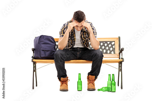 Young man with hangover sitting on a bench