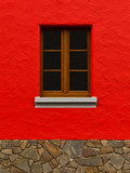 rote Mauer mit Bruchsteinsockel und Holzfenster