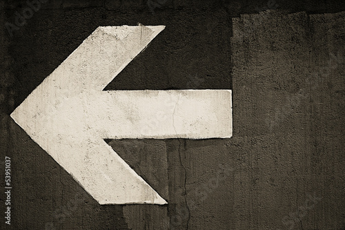 Arrow sign painted on a wall, grunge background in sepia tone
