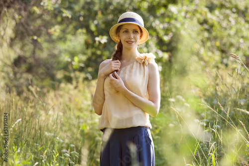 Beautiful happy woman among the tall grass