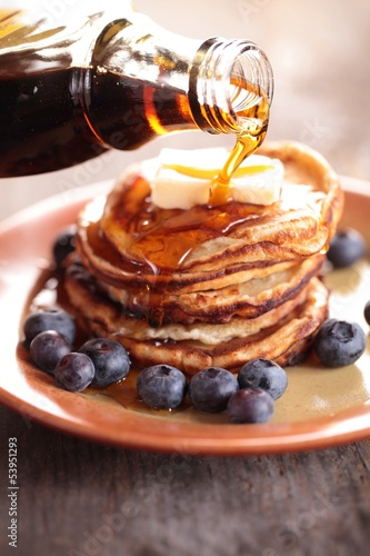 Close-up of pouring maple syrup on stack of pancakes.