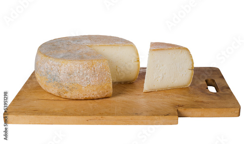 Traditional round farm cheese on wooden board