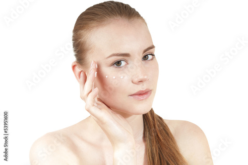 Young girl  applying moisturizer cream on her face. Isolated